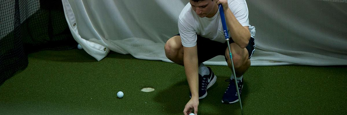 Header of a man placing a golf ball on a green in Yates.