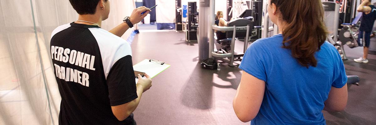 Header showing a personal trainer talking to a woman.