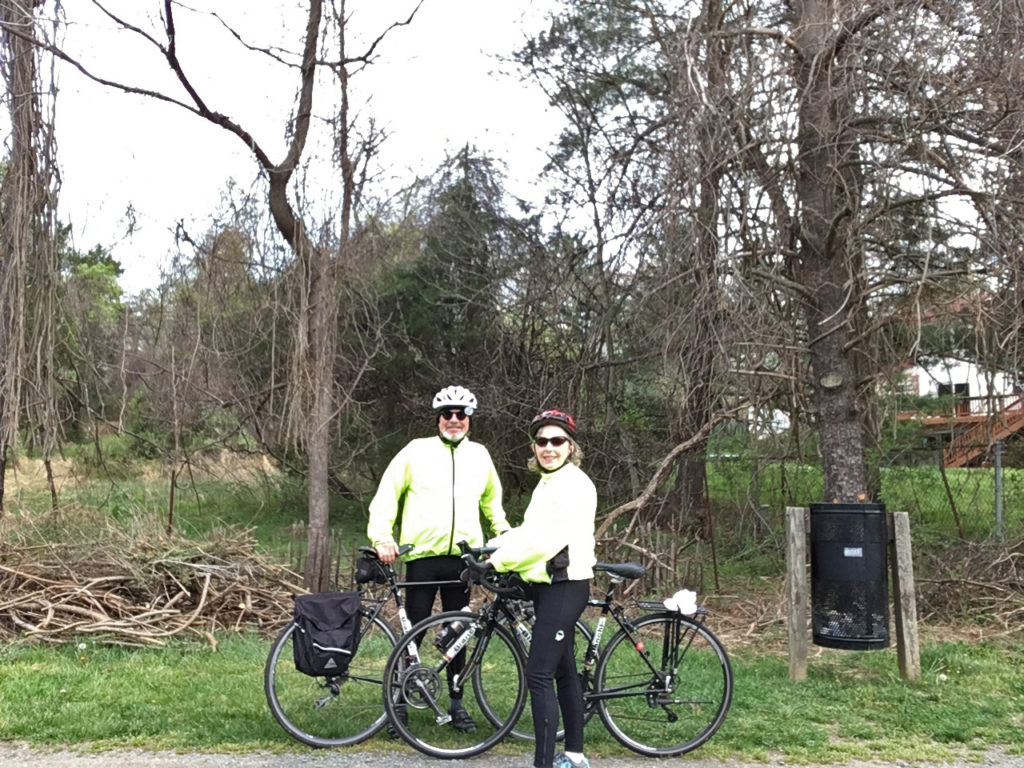 Mike & Sharon Adams posing for a picture on a bike trail with their bikes.