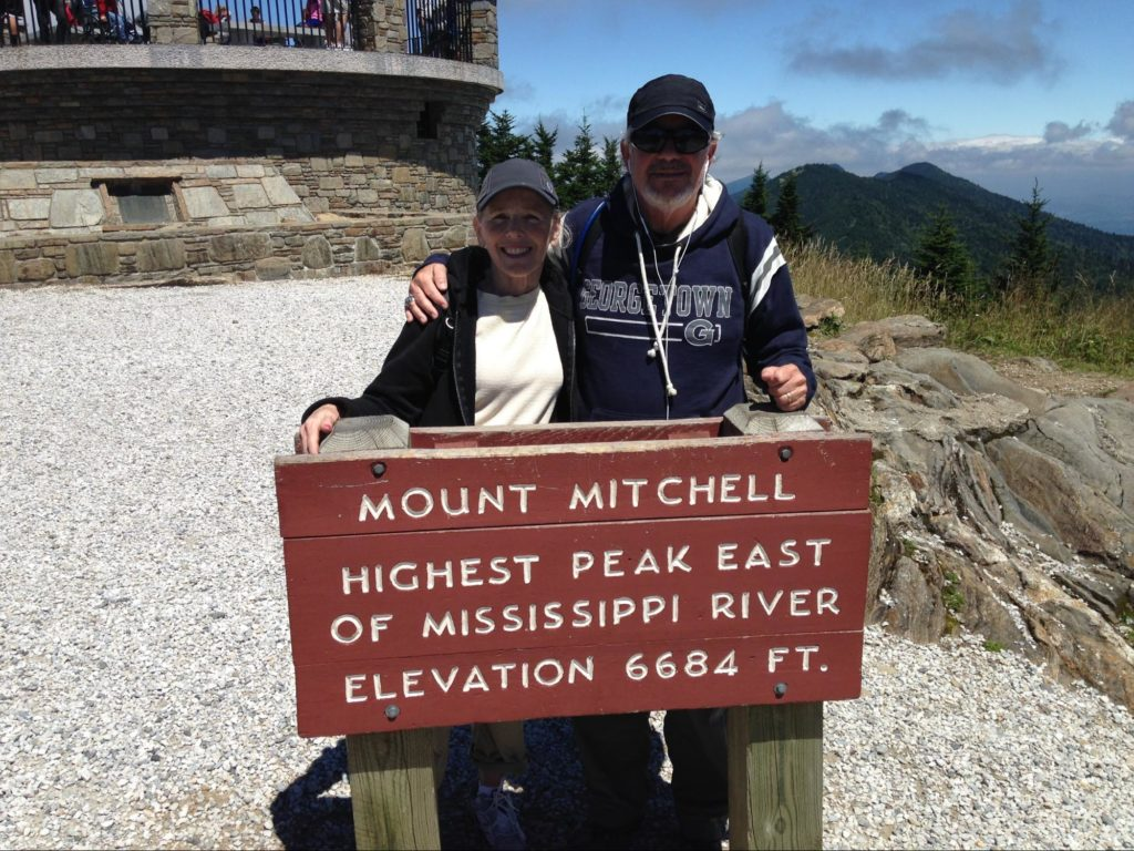 """Mike & Sharon Adams behind a sign saying """"Mount Mitchell Highest Peak East of Mississippi River Elevation 6684 FT."""""""