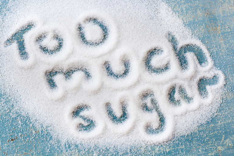 "The words ""too much sugar"" written in sugar grains.  Overhead view."
